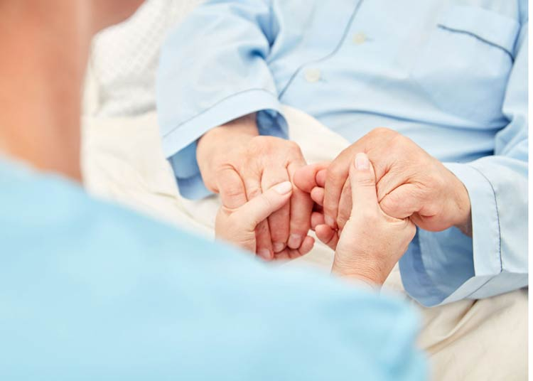 Nurse holding hands of patient in hospice care