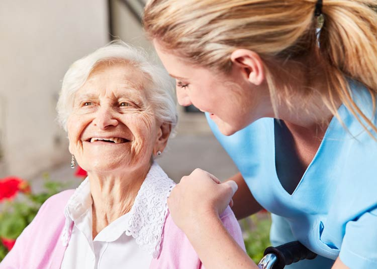 Young nurse smiling with elderly woman